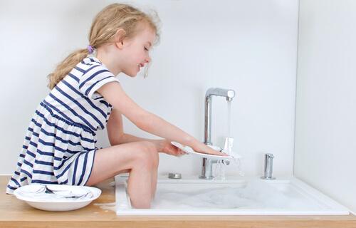 Holčička myje s úsměvem nádobí