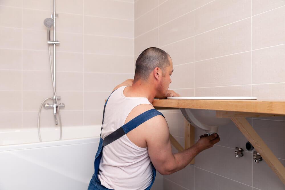 Instalatér připevňuje umyvadlo